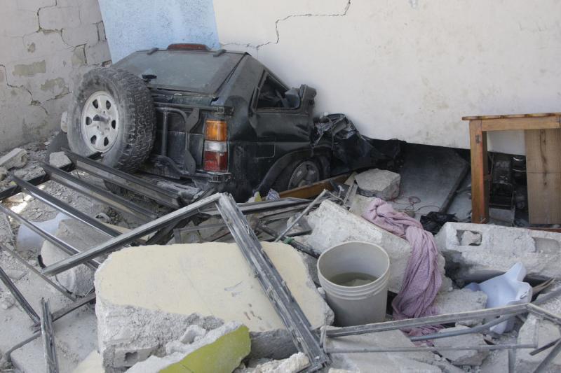 6. Разбитый автомобиль у полуразрушенного дома в Порт-о-Пренс 16 января 2010 года. (UPI/Anatoli Zhdanov)