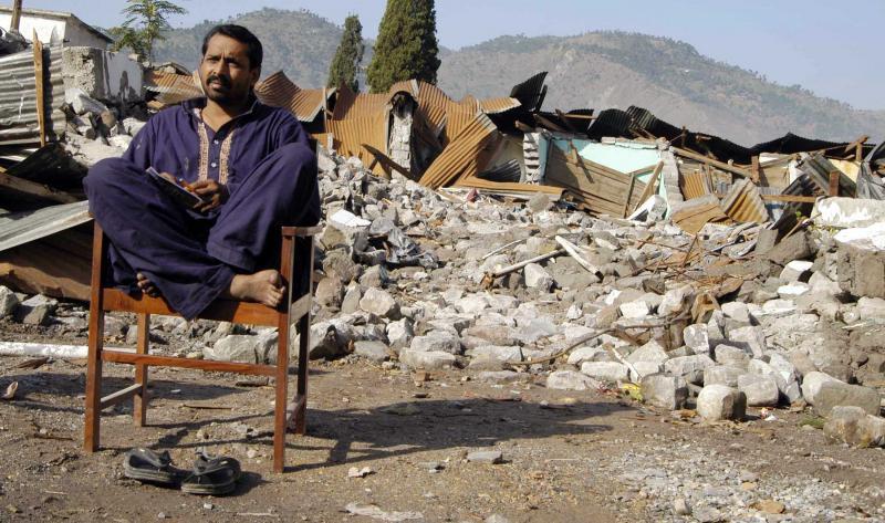 6) Пакистанец, выживший в землетрясении, сидит на стуле у своего разрушенного дома в Музаффарабаде 17 октября 2005 года. Два миллиона человек остались без домов после землетрясения, в результате которого погибло более 35 000 человек. (UPI Photo/Ahmad Abbasi)