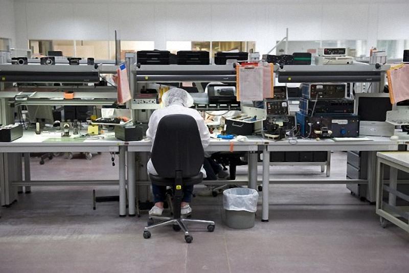 6) Рабочее место настроено на сборку аналоговых камер Leica. Но так как M8 и М9 имеют практически идентичный состав деталей, то собираются они параллельно с аналоговыми камерами. Весь процесс включает в себя 35 человек, и занимает около восьми часов на камеру. Крошечные частицы пыли внутри камеры, могут вызвать серьезные проблемы, поэтому завод Leica создал правила доступа к рабочему месту. Сотрудники носят низко-статическую обувь, чтобы избежать притягивание пыли. Пыле-поглощающее напольное покрытие находится на входах в сборочный цех. Все бумажные изделия на конвейере, рассматриваются в пластиковых пакетах чтобы, убедиться, что даже маленькие волокна, которое могут вырваться из страниц не смогут попасть в комнату. А сотрудники  вынуждены носить специальные шапочки.