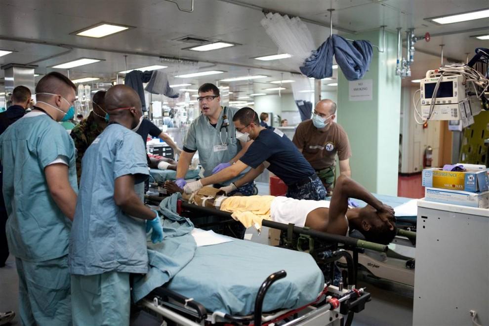 6. Военный врач проверяет пациента с подозрением на перелом бедра. Медицинский персонал состоит из 550 человек; в их числе – врачи всех специальностей, медсестры и санитары со всех концов США. На прошлой неделе в пятницу они были срочно вызваны в Балтимор, откуда «Comfort» взял курс на Гаити. (Brendan Hoffman / Getty Images)