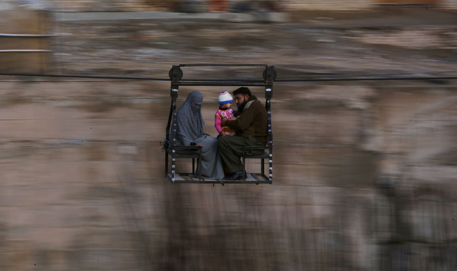 6) Пакистанская семья пересекает реку в кабинке канатной дороги в Равалпинди. (AP Photo/Muhammed Muheisen)