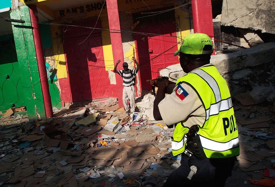 7) Гаитянский полицейского целится из винтовки в человека в центре делового района Порт-о-Пренс. В городе продолжается разгул грабежа и насилия. (Photo: Chris Hondros/Getty Images)