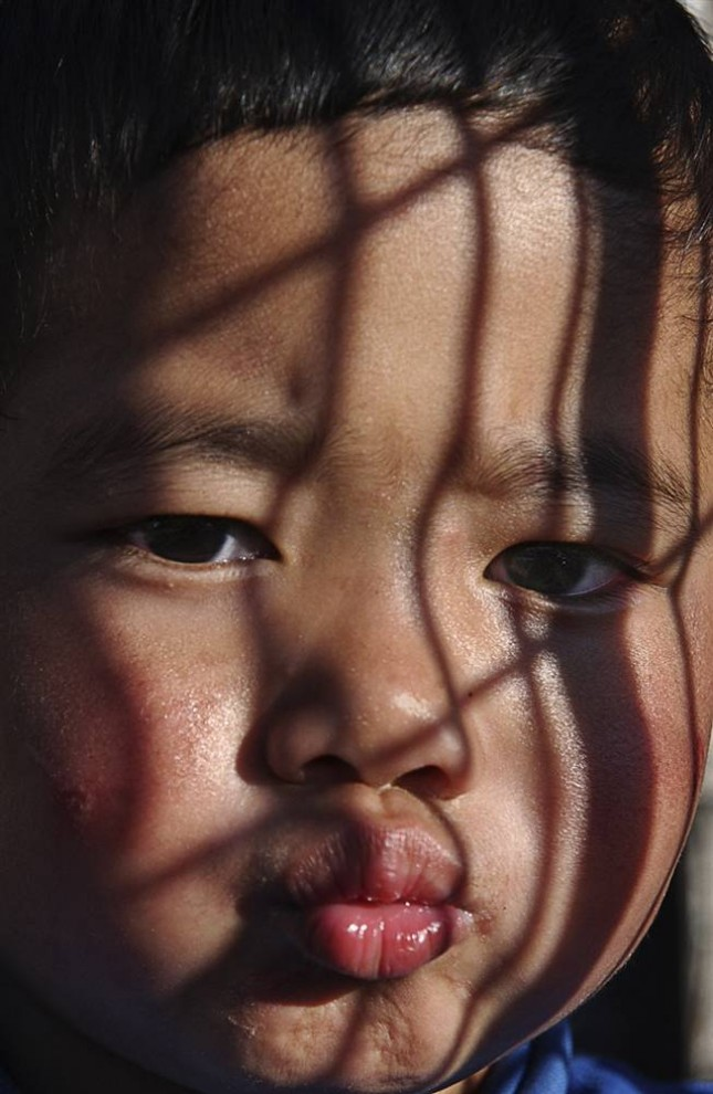 7) Задумчивый малыш из Деревни тибетских детей  в Дхарамсале, Индия, где заботятся о сиротах из Тибета.  (Bobby Sager / The Power of the Invisible Sun)