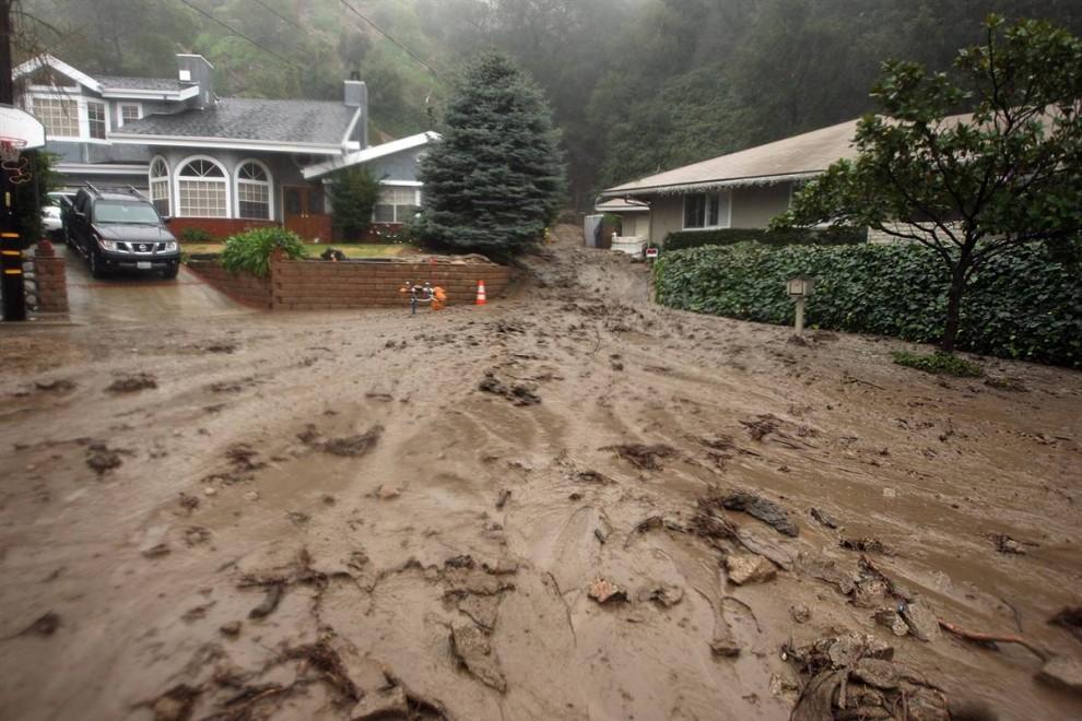 7. Грязь течет между домами на улице в эвакуированном районе 21 января в Ла Канада Флинтридж, Калифорния. (David Mcnew / Getty Images)