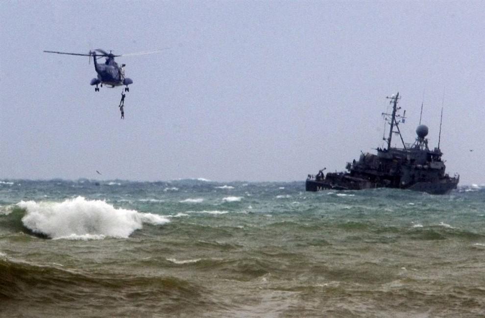 7) Ливанские командос достают один из трупов из воды, недалеко от вертолета - судно UNIFIL (Временные силы ООН в Ливане) осматривает район, в котором произошло крушение самолета в поисках тел и обломков. (Mohamed Azakir / Reuters)