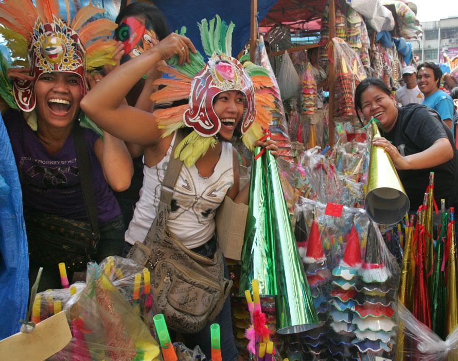 8. Группа уличных торговцев надели головные уборы и дуют в дудки, чтобы привлечь покупателей в торговом районе Манилы Дивисория, Филиппины. (AP Photo/Pat Roque)