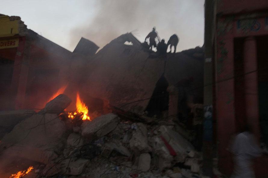 8) Мародеры обшаривают здание разрушенное во время землетрясения в воскресенье в Порт-о-Пренс, Гаити. Самолеты со спасателями и гуманитарной помощью были отправлены на Гаити. Страны во всем мире , в то время как  и учреждениям по оказанию помощи начал массированную операцию по оказанию помощи после мощного землетрясения, которое, возможно, погибли тысячи людей. (Фото: Joe Raedle/ Getty Images)