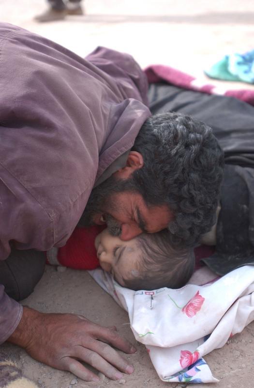 8) Мужчина оплакивает ребенка, погибшего в землетрясении в 6,6 баллов в Баме, Иран, 27 декабря 2003 года. (UPI Photo/Ali Khaligh)
