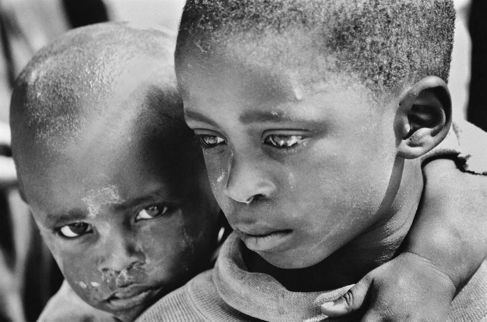 8) Снимок сделан в Руанде, неподалеку от Мурамби, возле мемориала жертвам геноцида, воздвигнутого в память о событиях более чем десятилетней давности, когда было убито 40000 человек. Мальчики кажутся не по годам серьезными.  (Bobby Sager / The Power of the Invisible Sun)