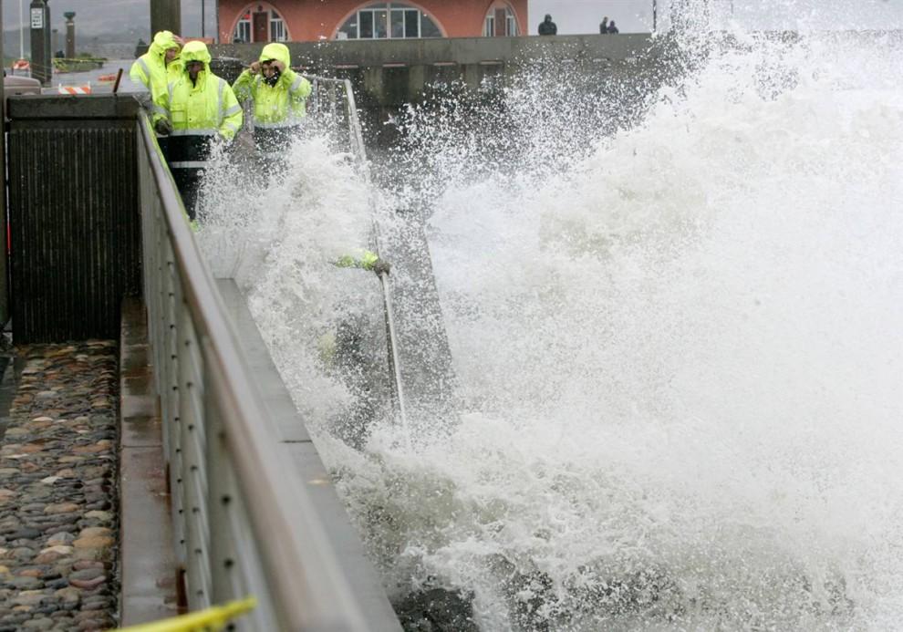 8. Городские рабочие Пацифики, штат Калифорния, пытаются восстановить разрушенную ураганом волноотбойную стену в четверг. (Marcio Jose Sanchez / AP)