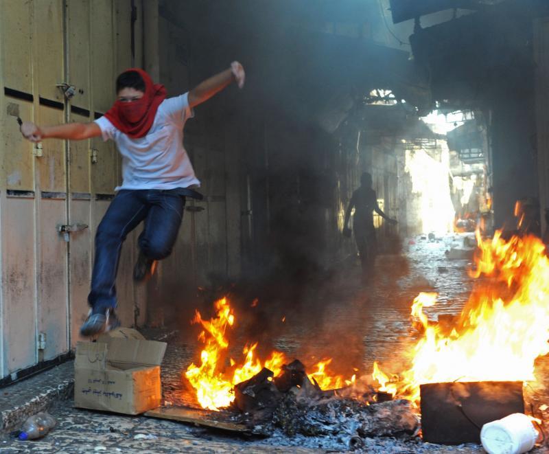 8. Арабский юноша в маске перепрыгивает через огонь, бросив камень в израильского полицейского в Иерусалиме 25 октября 2009 года. Конфликт разгорелся после того, как мусульманские лидеры подтолкнули арабов отдать мечеть Аль-акса в Иерусалиме «под еврейским напором (UPI/Debbie Hill)