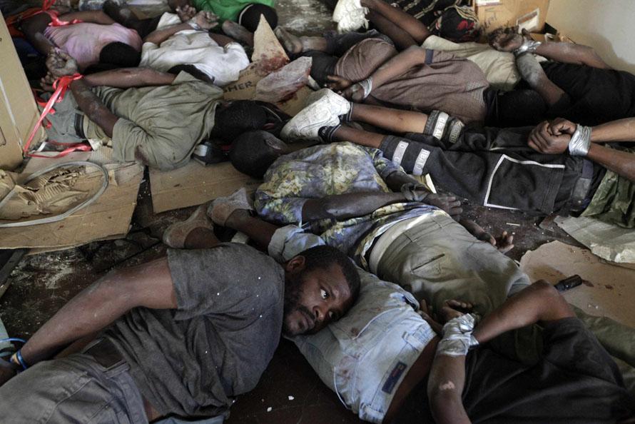 8) Подозреваемые в мародерстве лежат со связанными руками после задержания во время кражи бытовой техники из магазина в центре Порт-о-Пренс. (AP Photo/Ramon Espinosa)