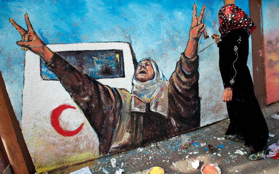 9. Палестинская девушка рисует фреску в честь годовщины боевых действий Израиля в Газе. (AP Photo/Hatem Moussa)