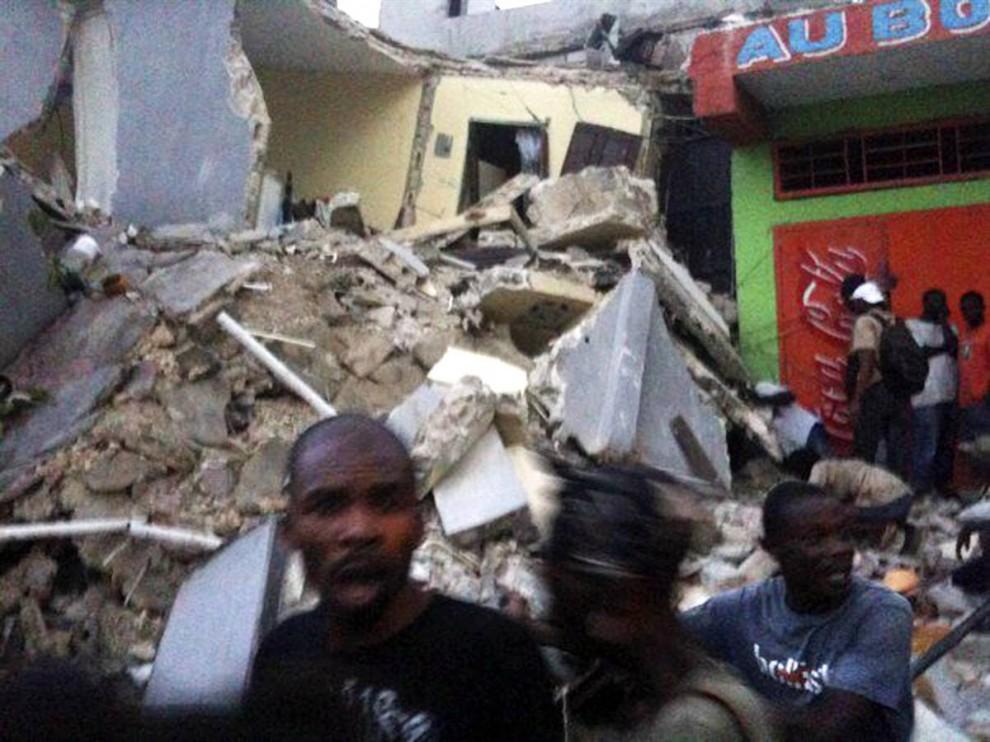 9. Люди пробегают мимо обломков разрушенного здания в Порт-о-Пренс 12 января. (Carel Pedre / AP)