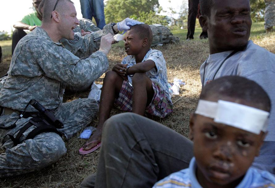 9) 11-летний Жан Гербер корчится от боли, когда медик Бадди Дэвис снимает повязку, чтобы проверить раны мальчика. Снимок сделан в загородном клубе, который  используется в качестве оперативной базы 82-й воздушно-десантной дивизией в Порт-о-Пренс. Многочисленные группы спасателей и медиков сконцентрировали свои усилия на помощи оставшимся в живых после мощного землетрясения, поразившего страну во вторник. (AP Photo/Jae C. Hong)
