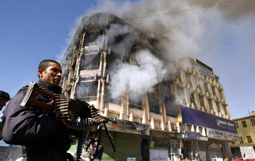 9. Афганский полицейский стоит перед торговым центром, где несколько часов шла перестрелка солдат с боевиками «Талибана», когда правительство установило контроль после теракта в понедельник. (Omar Sobhani / Reuters)