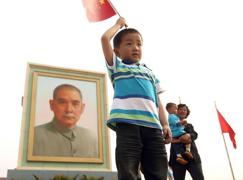 9. Китайский мальчик машет национальным флагом на площади Тяньаньмэнь, на которой каждый год выставляют огромный портрет Сунь Ятсена на майские праздники в Пекине 3 мая 2009 года. Сунь Ятсен считается историческим отцом современного Китая. (UPI Photo/Stephen Shaver)