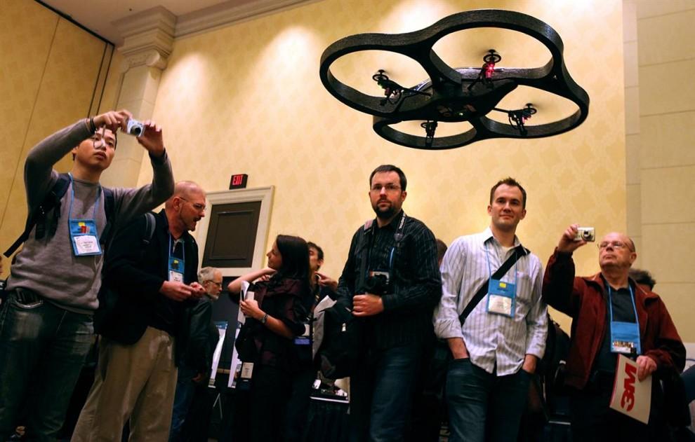 9. Посетители выставки CES смотрят на управляемую iPhone'ом летающую камеру «Parrot Air Drone» на пресс-конференции 5 января. Компания представляет свой продукт «Drone», как «убийственное приложение» для дополненной реальности. (Justin Sullivan / Getty Images)