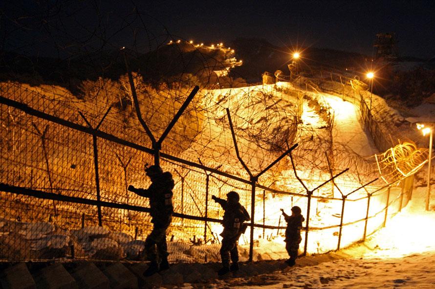 10. Солдаты южно-корейской армии идут вдоль забора с колючей проволокой рано утром в демилитаризованной зоне в Хвачоне к северу от Сеула. (AP Photo/Yonhap, Lee Sang-hack)