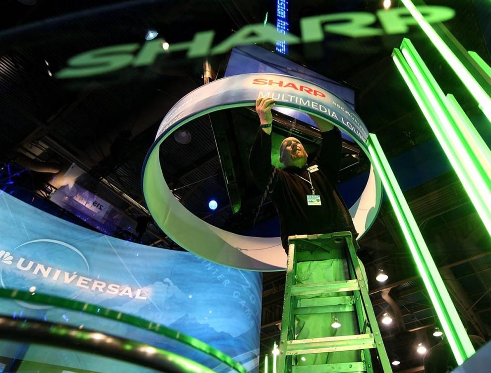 10. Джек Хора заканчивает подготовку продукта «Sharp Multimedia Lounge» внутри стенда компании «NBC Universal» 6 января. Крупнейшая в мире выставка технологий CES стартовала 7 января и продлится до 10 января. (Justin Sullivan / Getty Images)