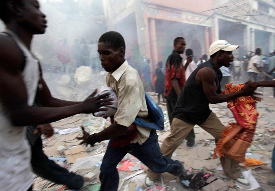 10) Мародеры дерутся за товары, которые они вытащили из рухнувших зданий в Порт-о-Пренс. (AP Photo/Julie Jacobson)