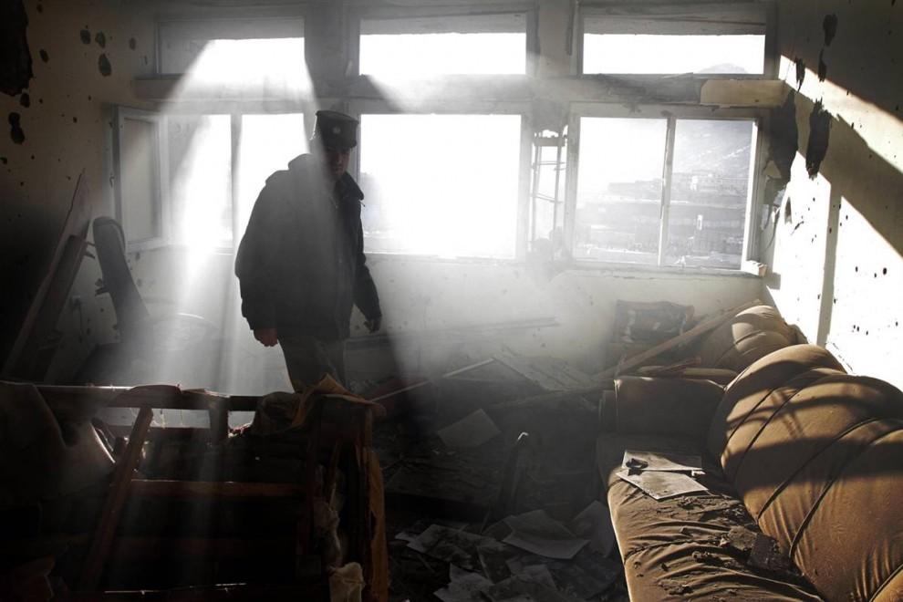 10. Афганский полицейский оценивает ущерб, нанесенный зданию после перестрелки с боевиками «Талибана» в Кабуле в понедельник. (Musadeq Sadeq / AP)