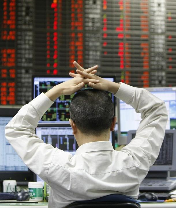 13) Дилер наблюдает за экранами в дилинговом зале Токийской Фондовой биржи. В последние годы на TSE не раз происходили компьютерные сбои, которые мешали трейдерам и, кроме того, отрицательно сказывались на репутации биржи.( REUTERS/Toru Hanai)