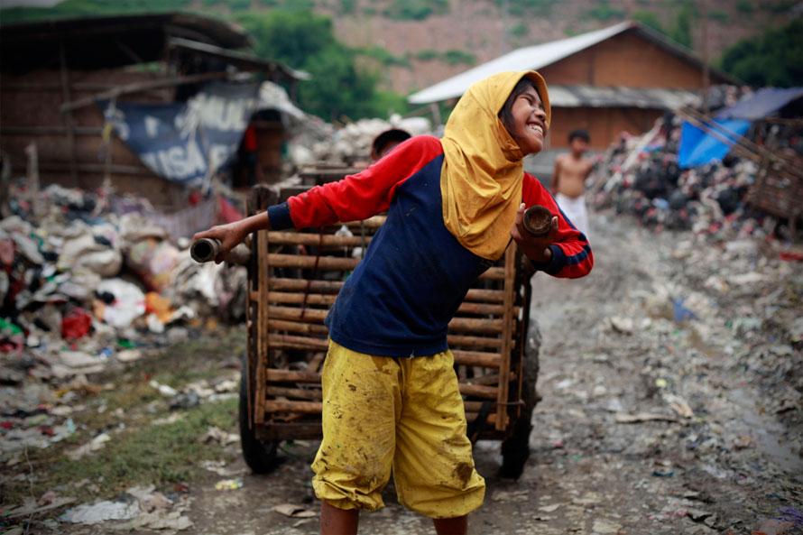 10) 11-летняя Нунг тянет корзины, которые будет использовать для сбора мусора на свалке Бантар Гебанг, одного из крупнейших мест для сброса отходов недалеко от Джакарты, столицы Индонезии. (Photo by Ulet Ifansasti/Getty Images)