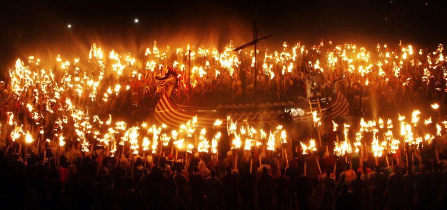11) Отряд ярлов в костюмах викингов собираются вокруг корабля во время традиционного фестиваля Апхелио на Шетландских островах в Шотландии. Апхелио проводится ежегодно в последний вторник января, и включает в себя целую серию парадов и собраний. Кульминацией праздника является сжигание корабля. (AP Photo/Danny Lawson, PA)