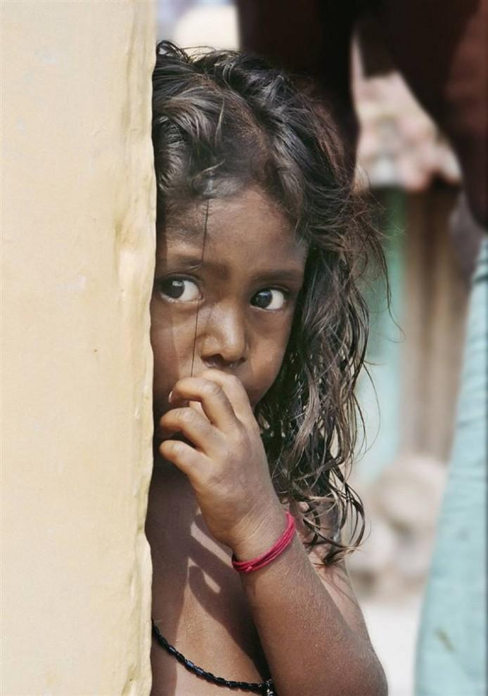 11) Девочка осторожно выглядывает из-за угла в разрушенном цунами городе Галле на Шри-Ланке.  (Bobby Sager / The Power of the Invisible Sun)