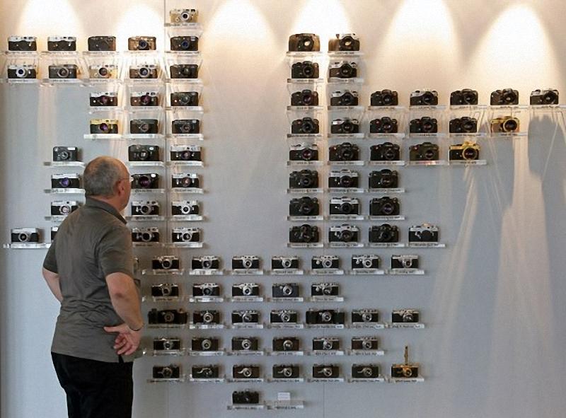11) Ральф Хагенауэр(Ralph Hagenauer), глава департамента по распространению продукции  компании Leica, рассматривает модельный ряд камер, в вестибюле центрального офиса.