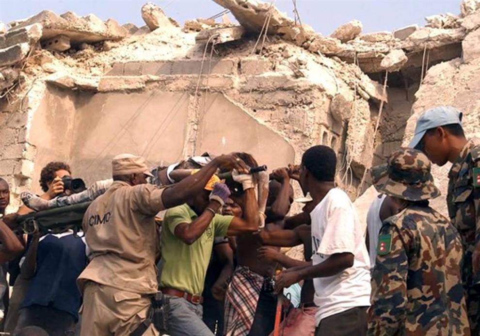 12. Гаитянцы несут на носилках раненого в Порт-о-Пренс 12 января. (AP)