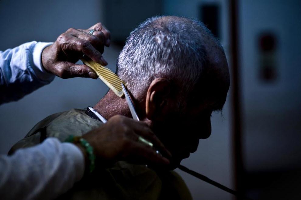 10. Мужчину подстригают в некоммерческой организации, предоставляющей бесплатные стрижки, чтобы поддержать безработных 19 января 2009 года в Осаке. (Shiho Fukada)