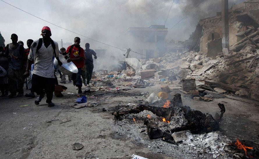 12) Гаитянцы несут краденый таз мимо горящего трупа на одной из улиц в Порт-о-Пренс. Спустя пять дней после мощного землетрясения, сотни жителей столицы продолжают грабить разрушенные магазины города. (AP Photo/Gregory Bull)