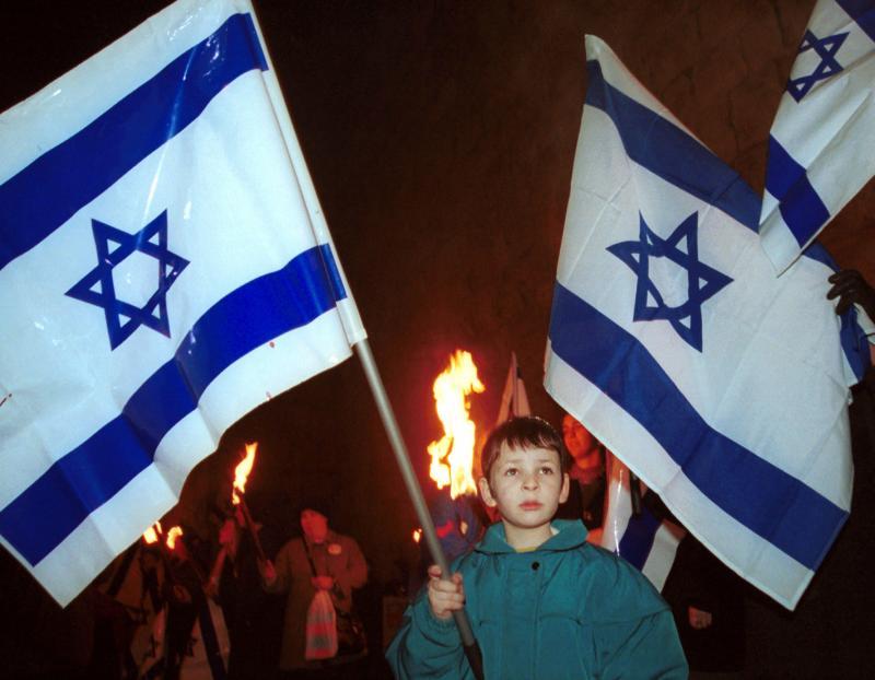 12. Израильский мальчик держит флаг у стен старого города Иерусалима недалеко от ворот Джаффа 8 января 2001 года во время митинга «Один Иерусалим», на который пришло 300 000 жителей Израиля. Тысячи израильтян окружили стены старого города в мирном соглашении с палестинцами. (rlw/dh/Debbie Hill/UPI)