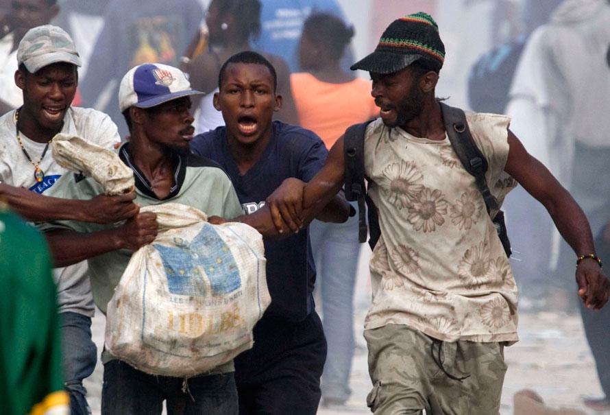13) Мародеры дерутся из-за мешка в гаитянской столице Порт-о-Пренс. Ситуация в Гаити усугубилась из-за мародерства и грабежей после разрушительного землетрясения 12 января. (AP Photo/Xinhua, David de la Paz)