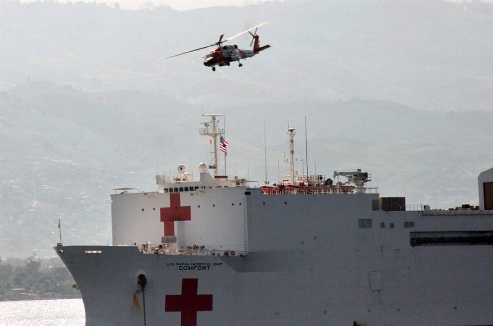 13. Вертолет привез новых раненых на борт плавучего госпиталя «Comfort» вскоре после того, как корабль пришвартовался у берегов Порт-о-Пренс. (U.S. Coast Guard via AFP - Getty Images)