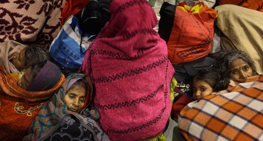14. Индийские пассажиры пытаются согреться, укутавшись в одеяла, на железнодорожной станции в Варанаси, Индия. Туман и морозы нарушили транспортную систему во многих частях северной Индии, а необычайно низкие температуры стали причиной смерти многих людей. (AP Photo/Rajesh Kumar Singh)