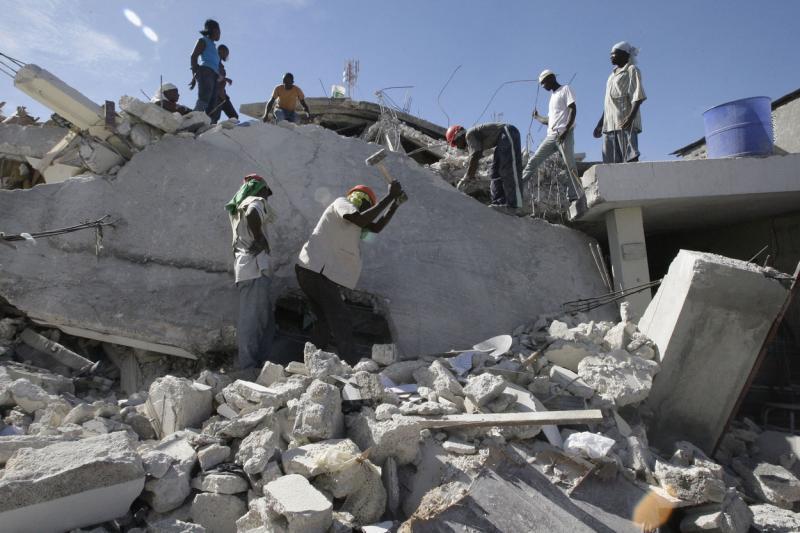 14. Люди ищут выживших в развалинах дома в Порт-о-Пренс 16 января 2010 года. (UPI/Anatoli Zhdanov)