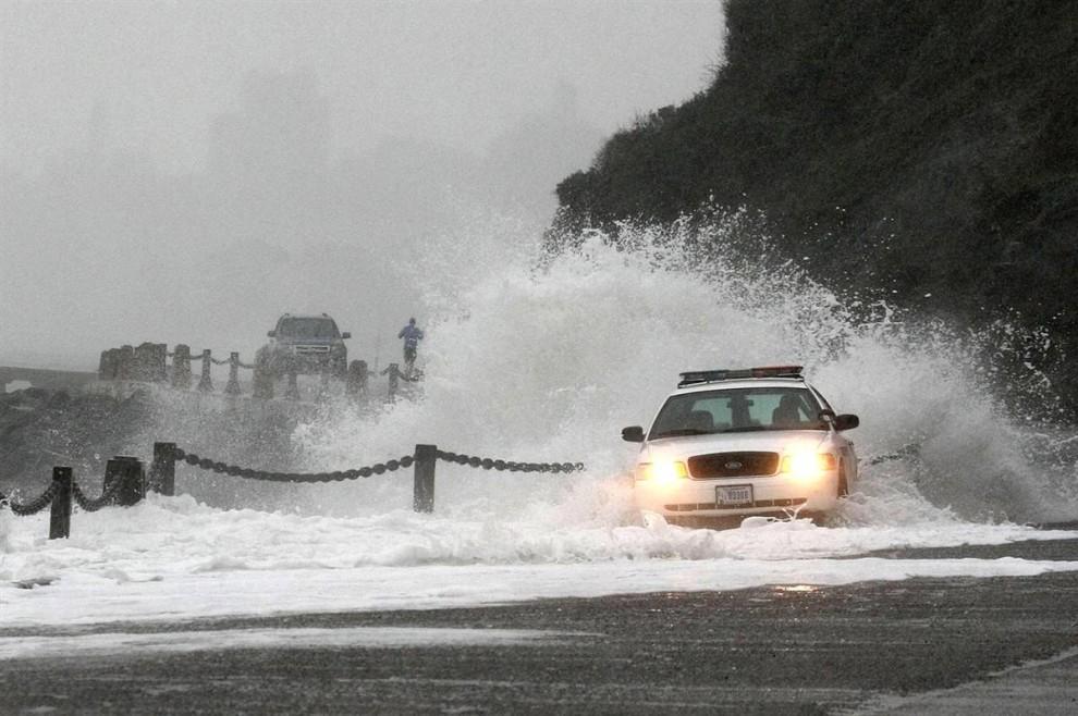 14. Волна накрывает патрульный полицейский автомобиль в Форт Пойнт в Сан-Франциско. (Justin Sullivan / Getty Images)