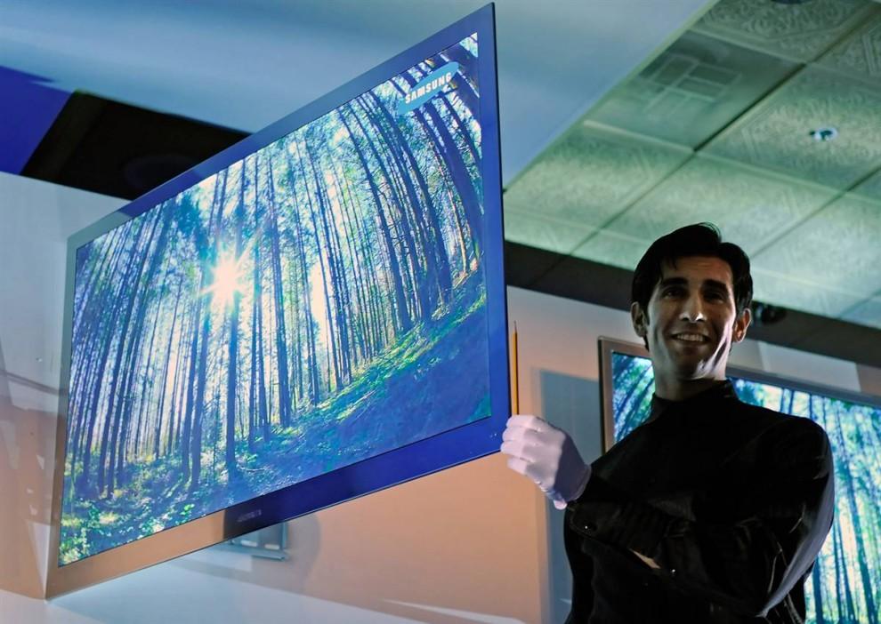 14. Сотрудник держит карандаш рядом с новым телевизором LED 9000 от компании «Samsung», чтобы продемонстрировать его толщину, на пресс-конференции 6 января. Телевизор имеет встроенную технологию 3-D и процессор, который может переводить 2-D в 3-D на ходу. (Ethan Miller / Getty Images)