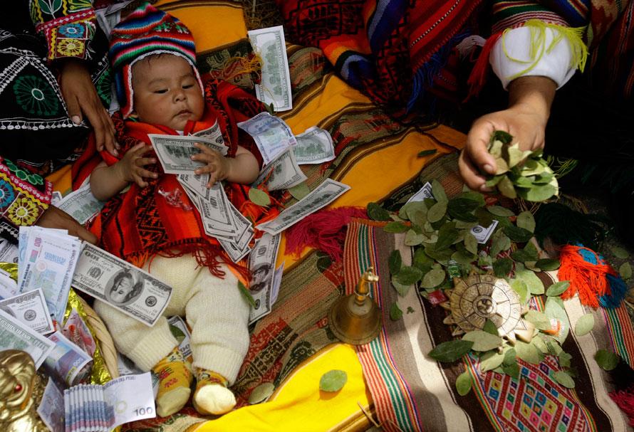 15. Ребенок, изображающий младенца Христа, лежит среди денег, пока мужчина, представляющий одного из трех волхвов, толкует предсказание по листьям коки на индейском рынке в Лиме. Богоявление, также называемое Днем трех волхвов, празднуется католиками в честь путешествия трех волхвов, пришедших почтить новорожденного Иисуса. (AP Photo/Martin Mejia)