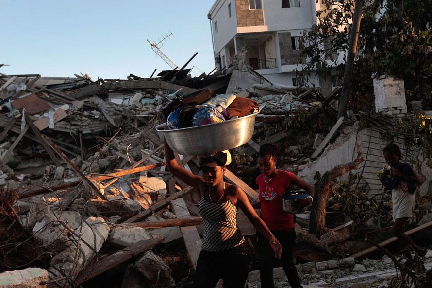 15) Гаитянские девушки несут продукты и товары через развалины возле Национального кафедрального собора в воскресенье в Порт-о-Пренс, Гаити. (Фото: Chris Hondros/Getty Images)