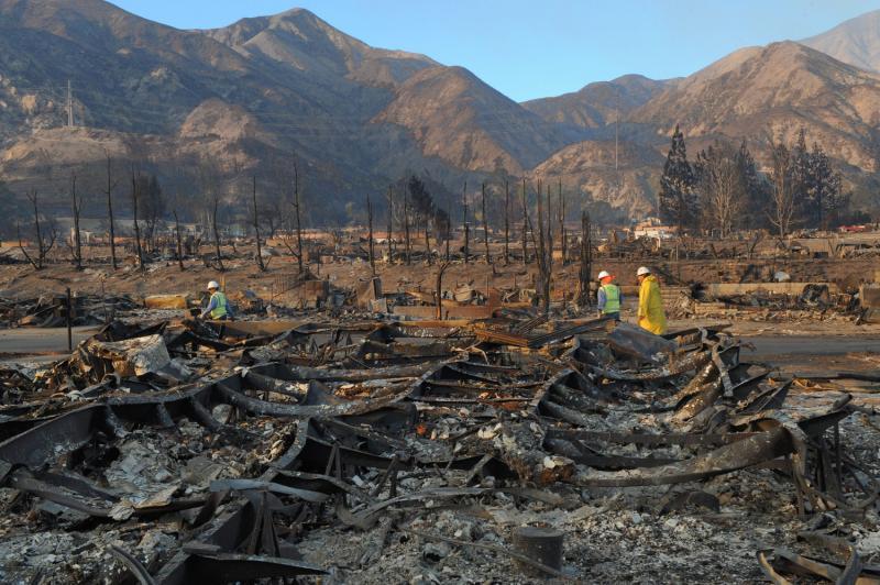 15) Рабочие перекрывают воду на стоянке жилых автофургонов в районе Силмар, Лос-Анджелес, 16 ноября 2008 года. Стоянка сгорела почти полностью в результате лесных пожаров. Было уничтожено более 500 автофургонов, от огня спаслось около 10 000 человек. (UPI Photo/Jim Ruymen)