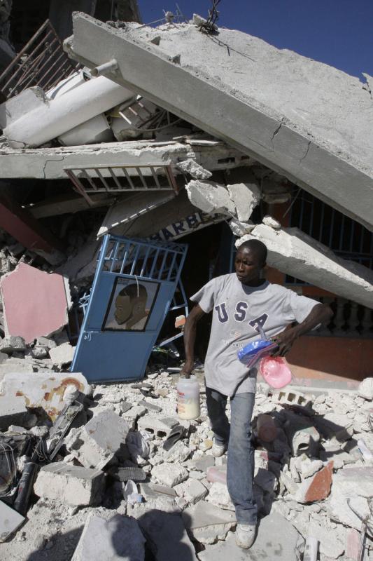 16. Человек идет по развалинам дома в Порт-о-Пренс, в котором сидел котенок. (UPI/Anatoli Zhdanov)