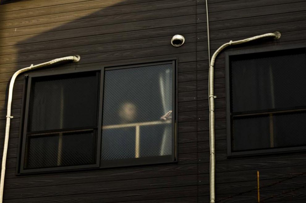 14. Мужчина стоит у окна 27 января 2009 года в Осаке. В этом районе самоубийства не редкость – люди часто выпрыгивают из окон. (Shiho Fukada)