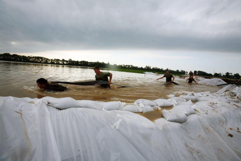 16) Американские морпехи и моряки тащат шланг по Уайт Ривер в Элноре, штат Индиана, 9 июня 2008 года. Члены 26-ого экспедиционного отряда национальной гвардии Индианы помогали властям и местным жителям поднять дамбу реки, чтобы предотвратить дальнейшее затопление района. (UPI Photo/Patrick M. Johnson-Campbell/U.S. Marine Corps)