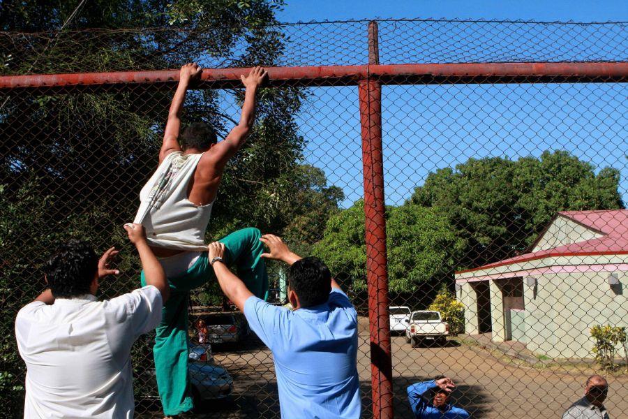 16. Служба охраны стаскивает пытавшегося бежать пациента с забора в психиатрической клинике Манагуа 3 февраля 2009 года. (AP Photo/Esteban Felix)
