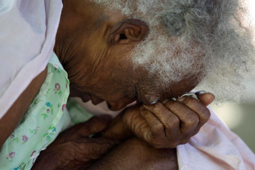 17) Старуха молится рядом с развалинами своего дома в Порт-о-Пренс. (AP Photo/Julie Jacobson)