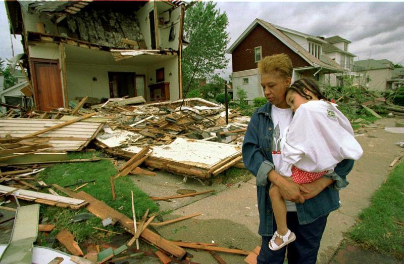 17) 3 июля 1997 года жительница Детройта Барбара Куинн держит свою 3-летнюю племянницу Тэйлор Джеймсон, осматривая соседний дом, сметенный торнадо. (UPI/bp/Bill Pugliano)